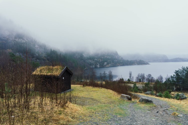 Image of a thatched house next a fjord surrounded by mountains and low cloud in Norway