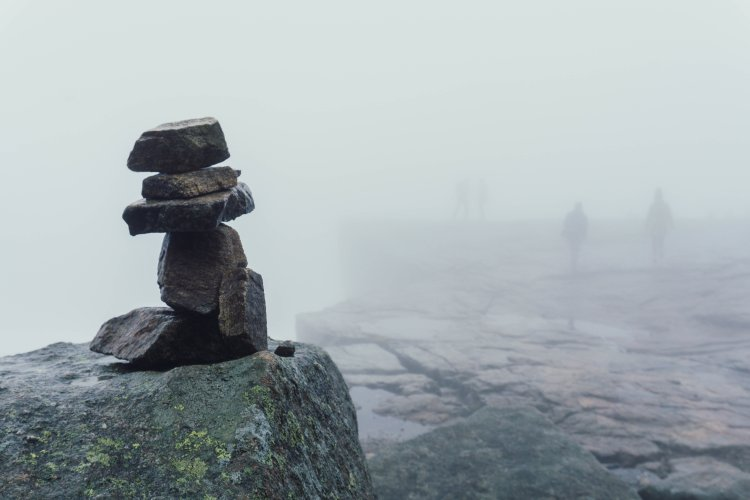 Image of stones piled in a column in the foreground with the outline of the top of Pulpit Rock in the foggy background
