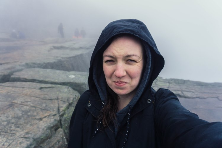 Image of me (Kat) looking unimpressed at the top of Pulpit Rock hike wearing a raincoat and jumper with no view in the background