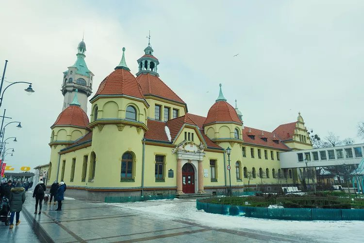 Image of large yellow building with red roof and green domes