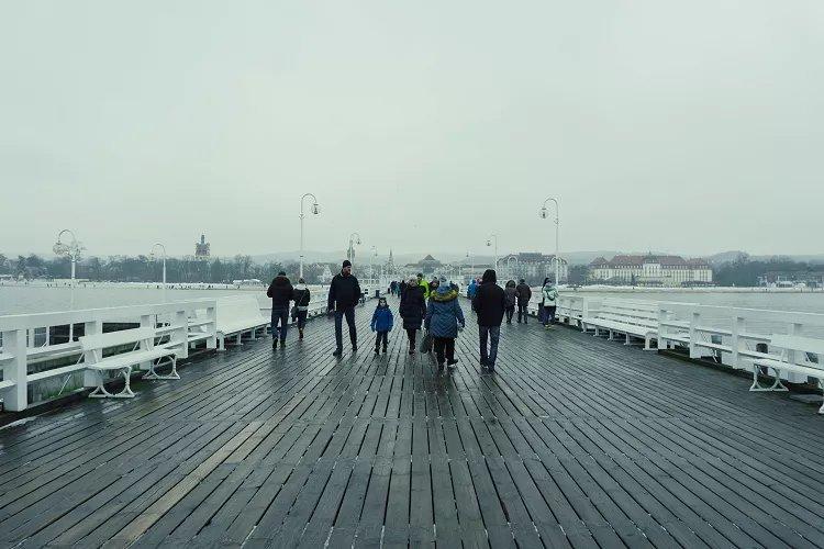 Image of people walking on a wide pier in Sopot in winter