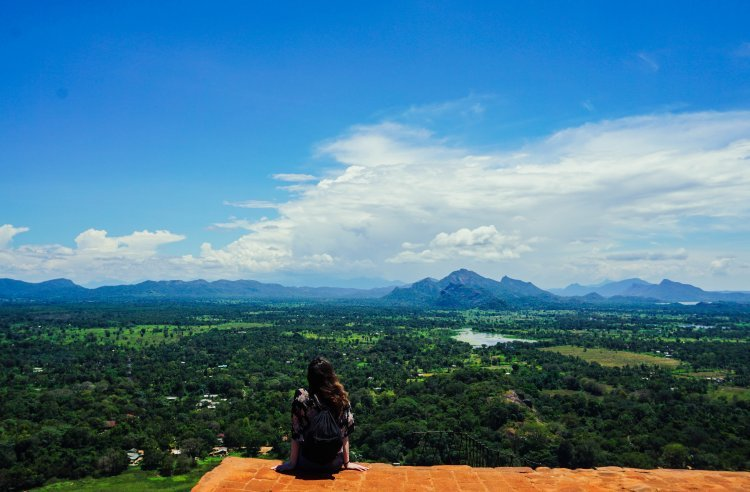 Image of me (Kat) sitting on the edge of the ruins at the top of Sigiriya Rock looking out at the view