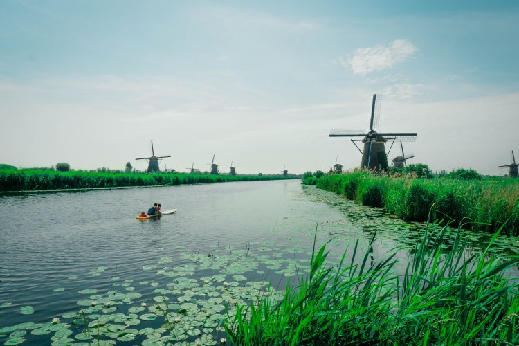 Image of kayak on the river with Kinderdijk windmills in background