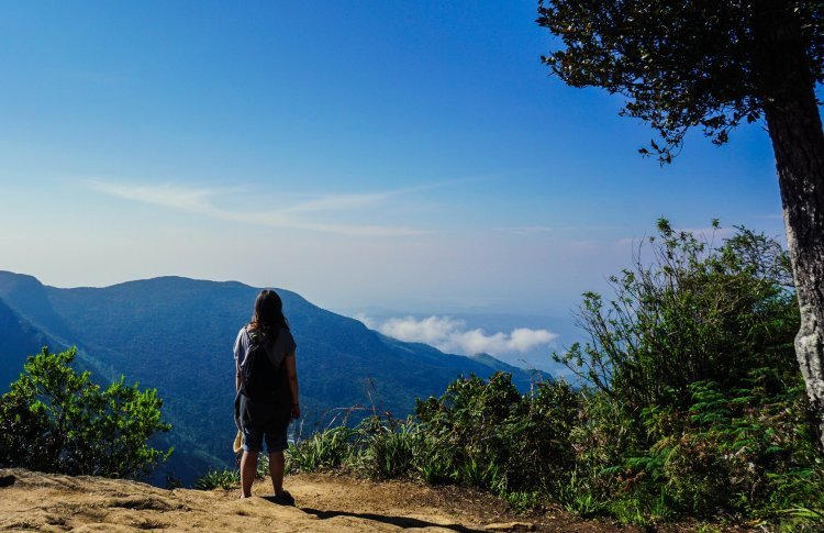 Image of girl standing on the edge at World's End in Sri Lanka with view of hills in background