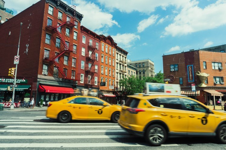 Image of road crossing at T-junction in Greenwich Village New York with yellow taxis out of focus in foreground