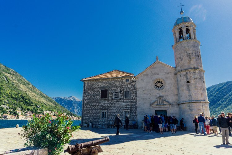 Image of church of Our Lady of the Rocks from the island with Perast, water and mountains in background.