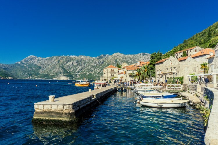 Image of Perast harbour with boats and Venetian style buildings on the edge of the water with mountains in background