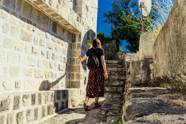 Image of Kat walking up cobbled stairs in backstreets of Perast