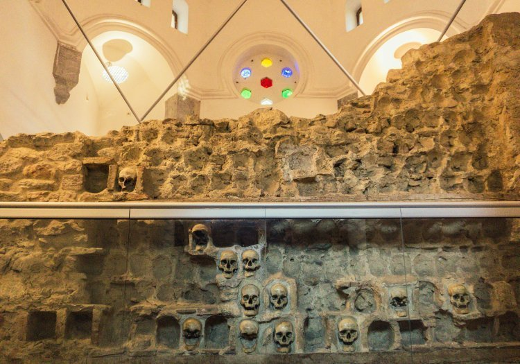 Close up of one of the walls of the Skull Tower with some skulls and many empty caverns where skulls once were.