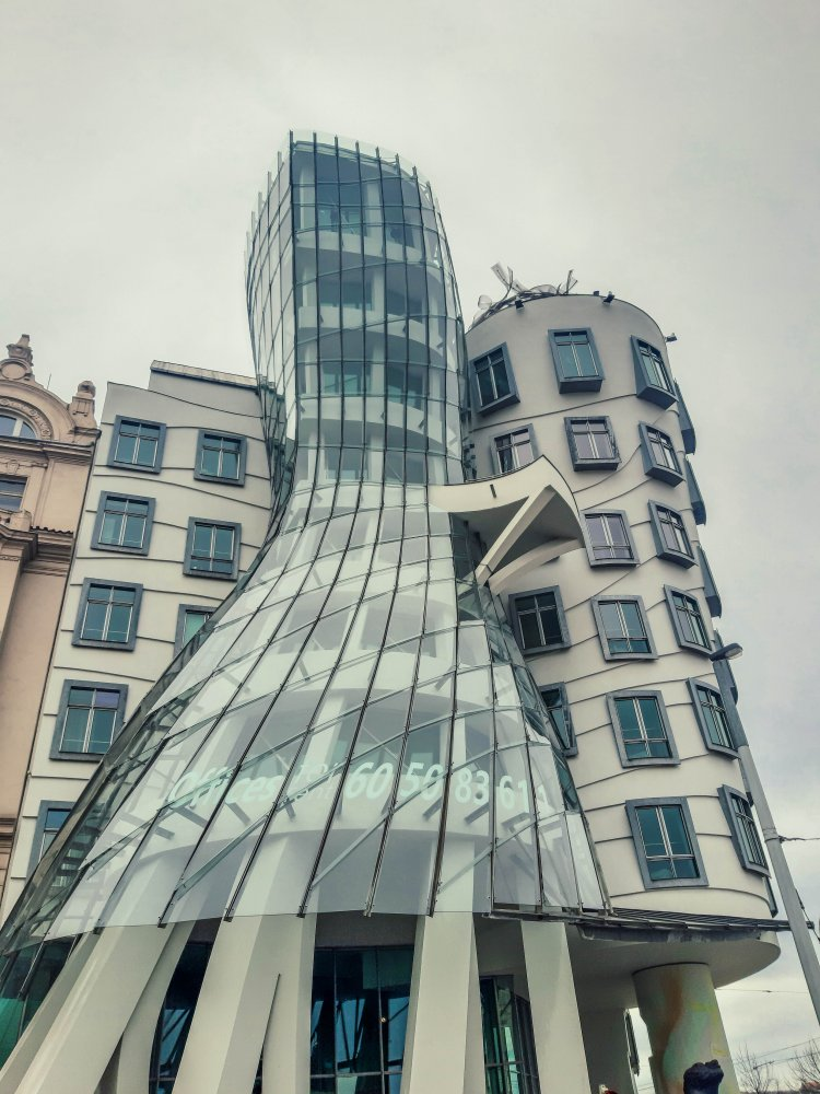 Modern glass curved building next to cylinder shaped traditional building with many windows. Together they make up the Dancing House in Prague.