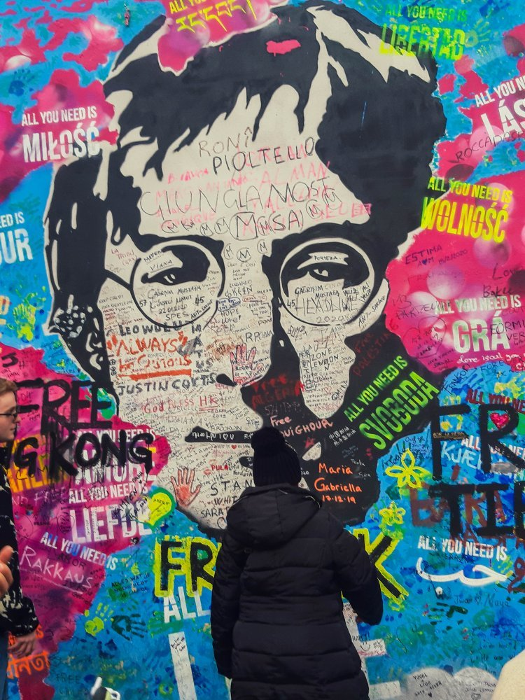 Person standing in front of large mural of John Lennon painted on the Lennon Wall in Prague