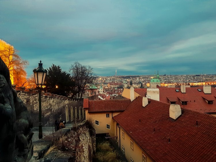 View from the top of Prague Castle looking down the steps and out over the city lit up at night.